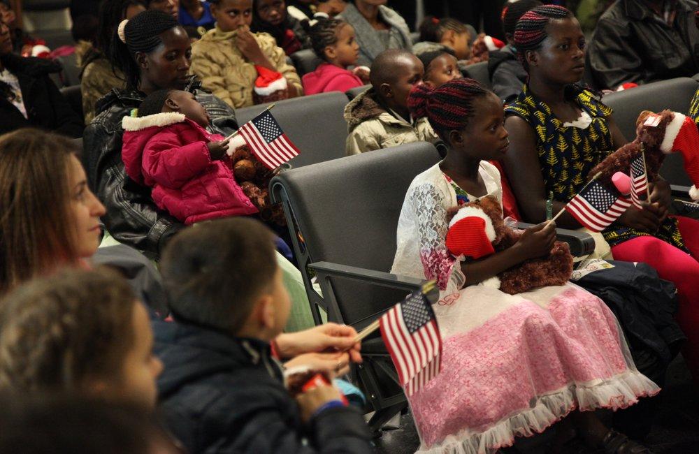 Беженцы из Украины, Сомали и Эритреи на приветственной церемонии МОМ в аэропорту им. Кеннеди в Нью-Йорке